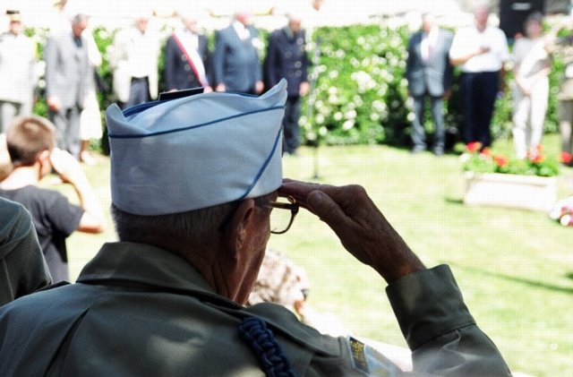 US airborne veteran salutes at a D Day memorial in Normandy 2004